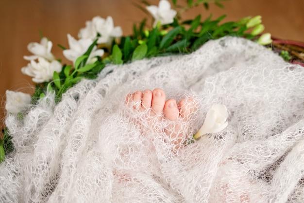 Крупным планом изображение ножек новорожденного на вязаный плед и цветы Premium Фотографии