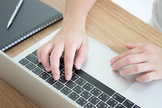 Крупным планом фотографии рук, которые работают на столе с ноутбуком. передний план. Premium Фотографии