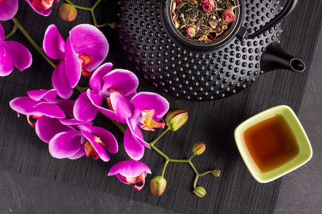 Close-up of pink orchid flower and dry herb tea on place mat Free Photo