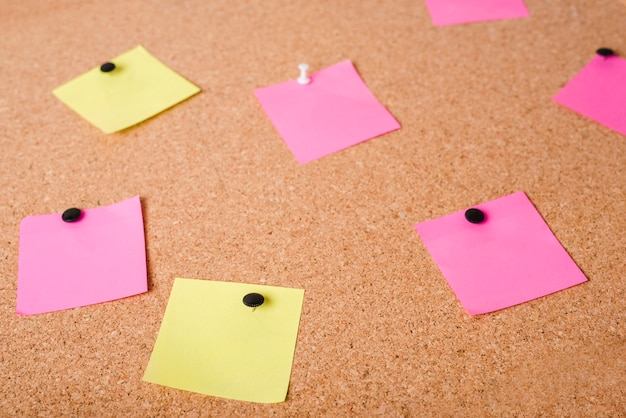 Close-up of pink and yellow adhesive notes on corkboard Free Photo