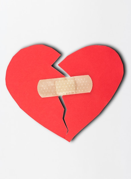 Close up of plaster and paper broken heart on white background. Premium Photo