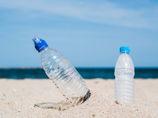 Close-up of plastic water bottles stuck in sand at beach Free Photo