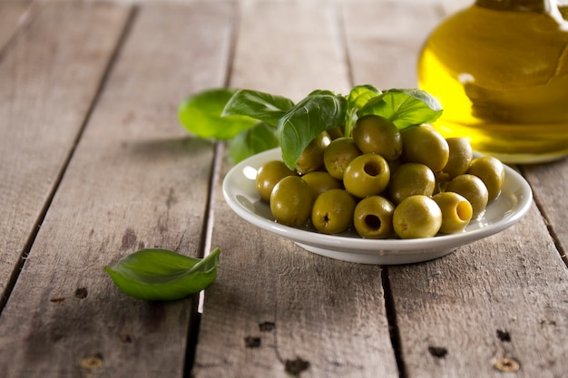 Close-up of plate with olives on wooden surface Free Photo