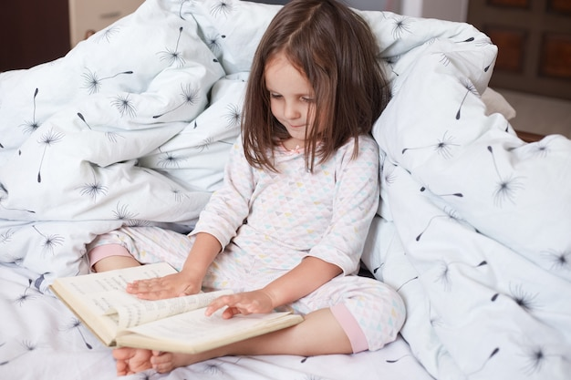 Close up portait of little girl sittng in bed, wearing pajama, charming female kid with dark hair, holding bookin hand and reading it, child looking at her book, reads interestin fairy tale. Premium Photo