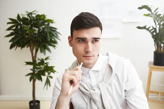 Крупным планом портрет красивого чисто выбритого молодого европейского дизайнера-мужчины с задумчивым взглядом во время работы на своем рабочем месте, обдумывающего новые идеи и решения. люди, работа, талант и творчество Бесплатные Фотографии