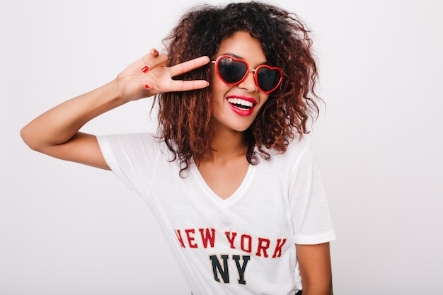 Ritratto del primo piano del modello femminile nero attraente con il manicure rosso isolato. foto della ragazza africana felice in occhiali da sole in posa con il segno di pace. Foto Gratuite