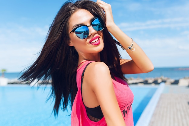 Close-up portrait of attractive brunette girl with long hair standing near pool. she is touching hair and looking to the camera. Free Photo