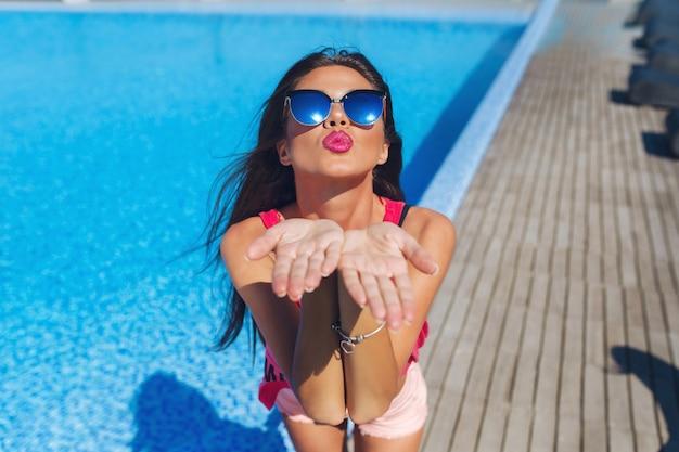 Ritratto del primo piano della ragazza attraente del brunette con capelli lunghi che stanno vicino alla piscina. allunga le mani verso la telecamera e fa un bacio. Foto Gratuite