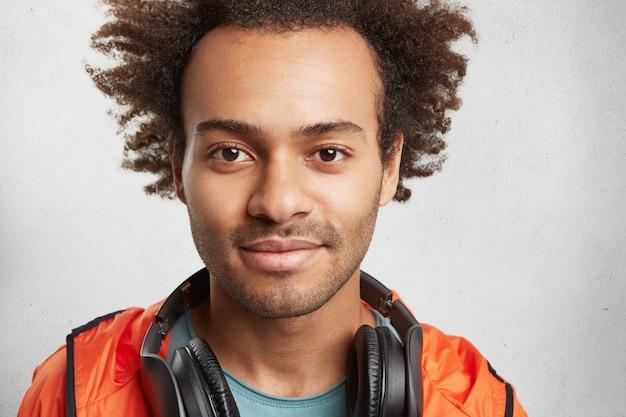 Close up ritratto di uomo attraente con acconciatura afro, stoppie, indossa giacca a vento arancione Foto Gratuite
