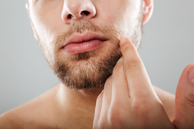 Close up portrait of bearded half men's face with hand Free Photo