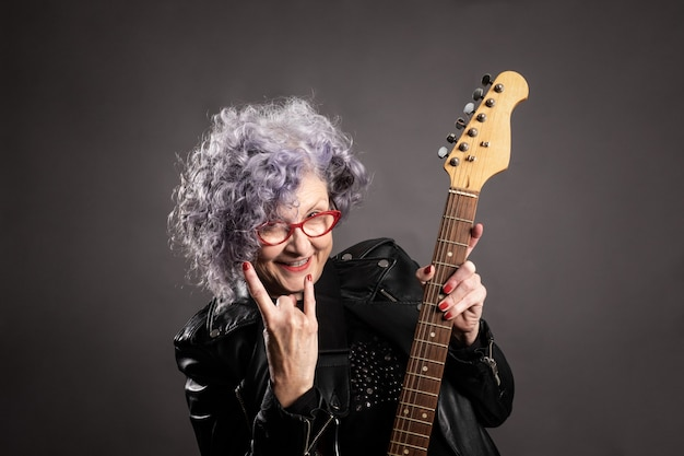 Close up portrait of beautiful older woman holding an electric guitar Premium Photo