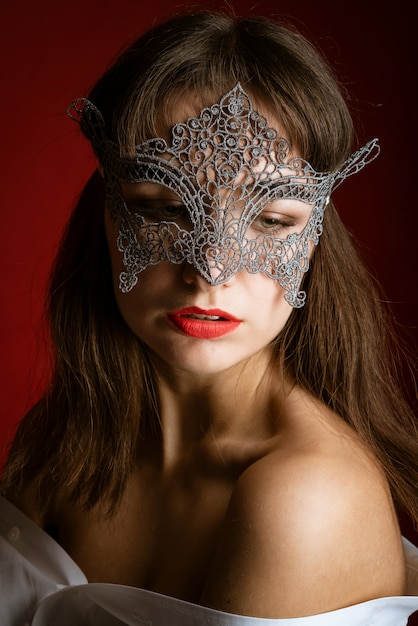 Close-up portrait of a beautiful sexy woman in a mask on a red background, red lips Premium Photo
