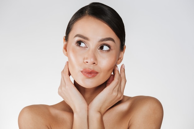 Close up portrait of beautiful woman with natural makeup looking aside and holding hands close to her healthy face, isolated over white Free Photo