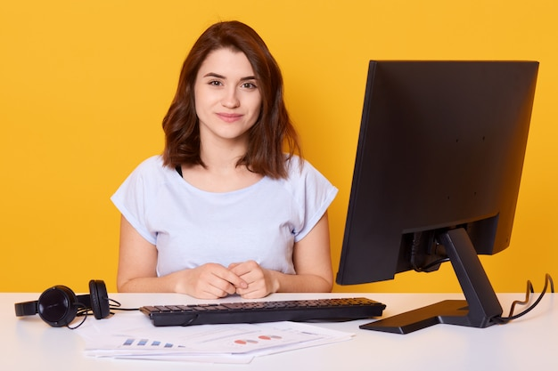 Close up portrait of beautiful young brunette female sitting at white desk in front of computer at home Free Photo
