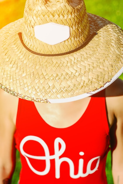 Close up portrait of a beautiful young woman in sexy red swimsuit and vogue vintage straw hat. Premium Photo