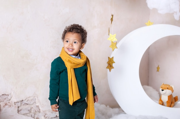 Close-up portrait of a black boy face, afro-american little boy. little black boy is smiling. cute baby, baby in game. pretty smile. curly hair. mulat. adventures of the little prince in the month. Premium Photo