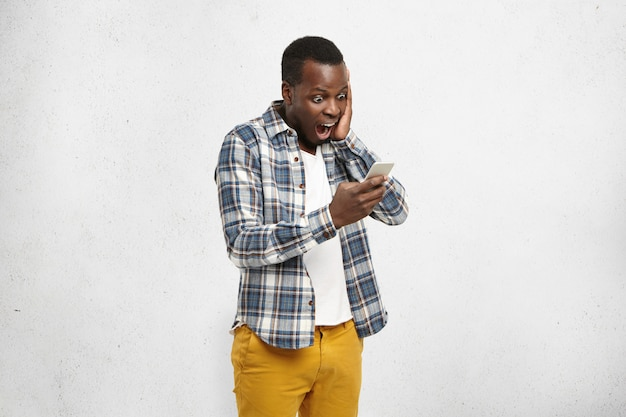 Close up portrait of black shocked hipster in stylish and trendy yellow pants, holding smartphone in one hand touching his head Free Photo