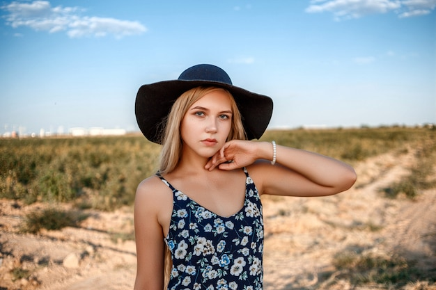 A close-up portrait of a blue-eyed blonde woman in a black hat and a floral print dress.she's posing in a vineyard during sunset Premium Photo