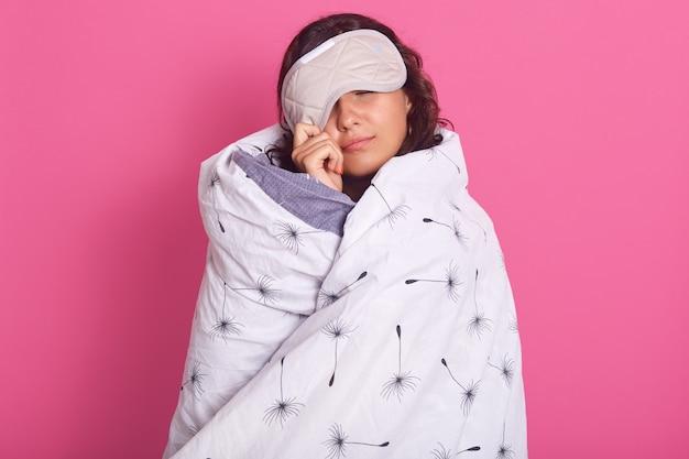 Primo piano ritratto di donna bruna che fa capolino dalla maschera per dormire, non vuole svegliarsi, tiene gli occhi chiusi, indossa una coperta bianca Foto Gratuite