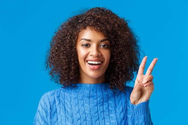休日を祝う、のんきな、幸せな楽しい女性のクローズアップの肖像画、みんなに良い新年を願って、ピースサインを示し、嬉しそうに笑って、セーターを着て、積極性と喜びを表現します。 無料写真