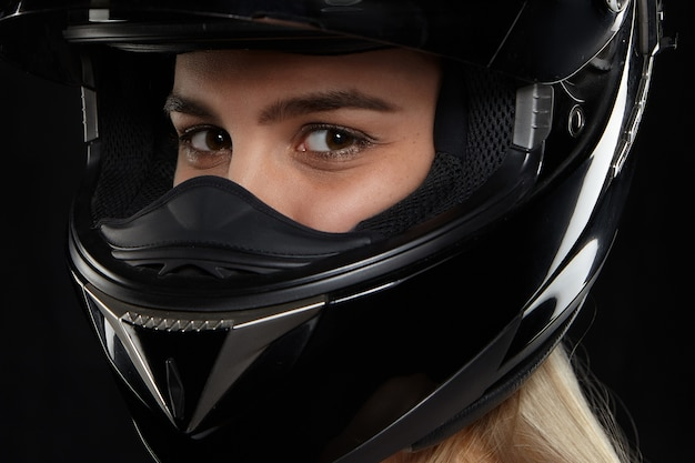 Close up portrait of caucasian female motorcycle racer with happy eyes wearing black modern safety helmet, going to competition, feeling excited. speed, extreme, danger and activity concept Free Photo