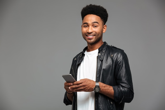 Close-up portrait of cheerful african guy with stylich haircut holding mobile phone, looking Free Photo
