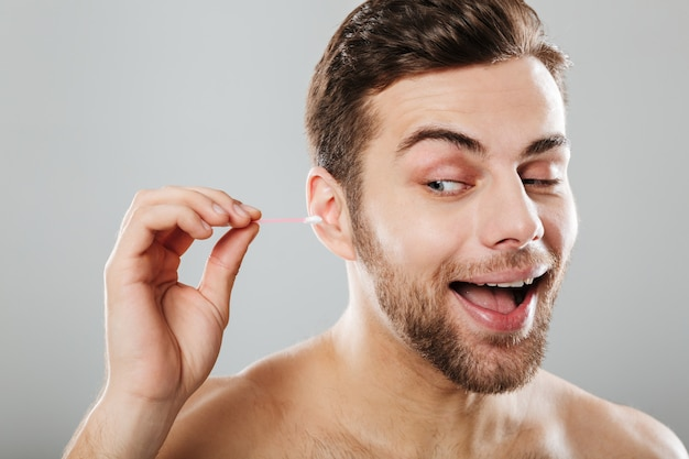 Close up portrait of a cheery man cleaning his ears Free Photo