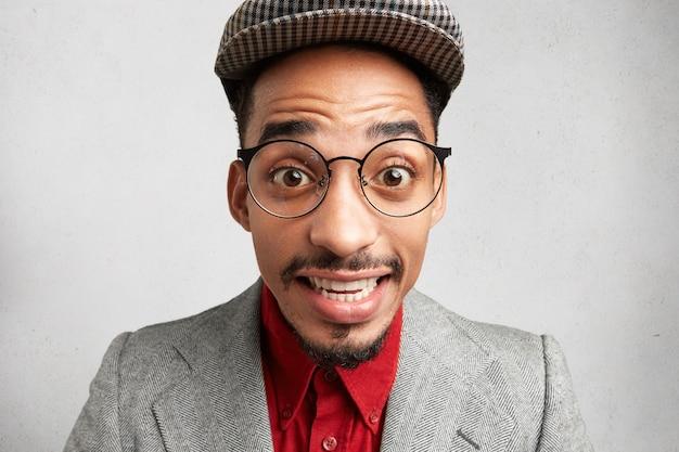 Close up ritratto di maldestro maschio comico indossa grandi occhiali, berretto e giacca, sorride con sorpresa, Foto Gratuite