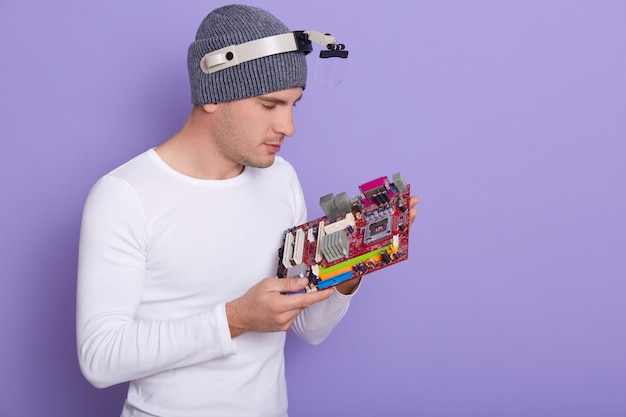 Close up portrait of concentrated electronics engineer with magnifying glass on his head Free Photo