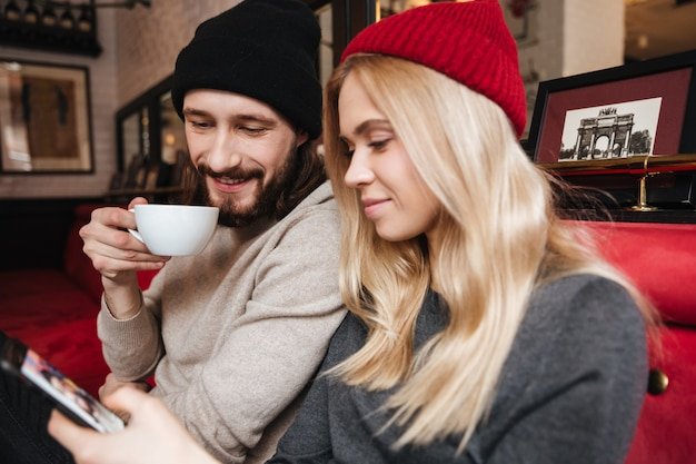 Close up portrait of couple looking at phone in cafe Free Photo