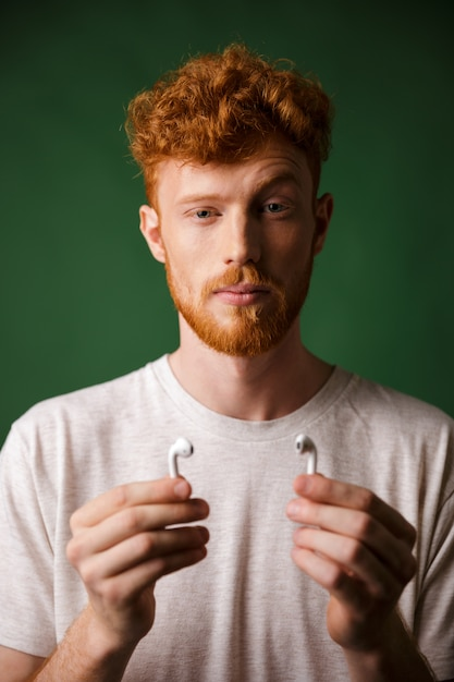 Close-up portrait of curly redhead man with raised eyebrow, showing his airpods, Free Photo