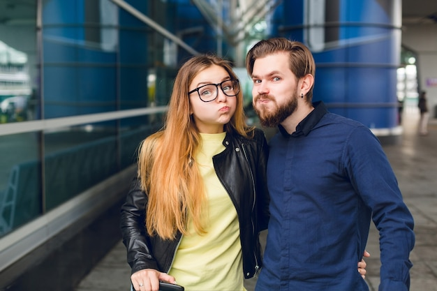 Ritratto del primo piano di coppia carina in piedi fuori in aeroporto. ha capelli lunghi, occhiali, maglione giallo, giacca. indossa camicia nera, barba. si stanno abbracciando e scimmiottando verso la telecamera. Foto Gratuite