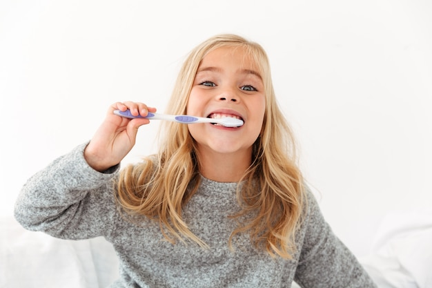 Close-up portrait of cute kid in gray pajamas brushing her teeth Free Photo