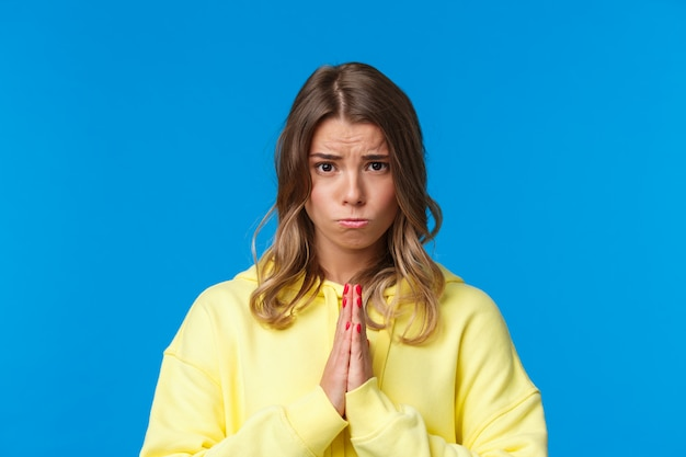 Close-up portrait of cute sulky european female blonde begging for help, asking favour, really need something, holding hands in pray, frowing and sobbing as plead for apology, blue wall Premium Photo