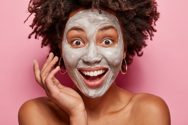 Close up portrait of delighted afro american lady has white clay mask on face, smiles broadly, surprised to have fresh skin after beauty procedures, has consultancy with beautician or cosmetologist Free Photo