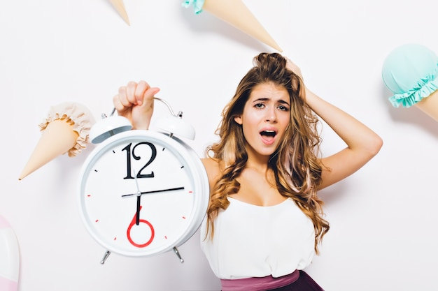 Close-up portrait of dismayed brunette woman in stylish outfit touching hair and holding big clock. stunning young woman emotionally posing on decorated wall with ice cream. Free Photo