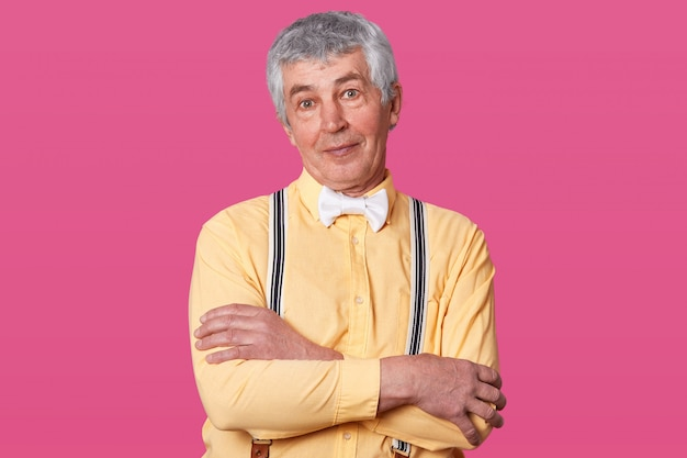 Close up portrait of eldery man with yellow shirt and white bow tie, looking directly at camera, keeps hands folded, free spase for your advertisment or promotion, isolated on rose studio. Free Photo