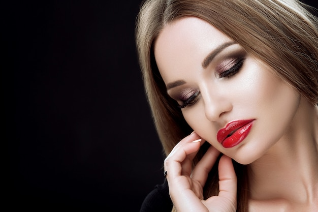 Close-up portrait of an elegant woman with bright makeup, red lips,long lashes, straight long hair, perfect eyebrows, manicure. Premium Photo
