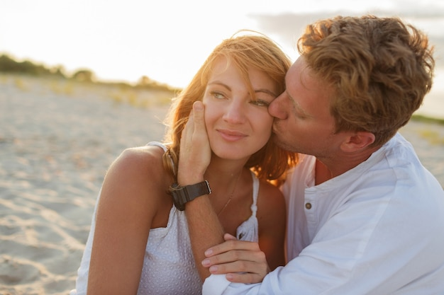 Close up portrait of european beautiful couple embracing against sunset. Free Photo