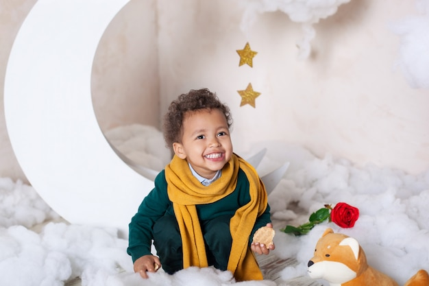 A close-up portrait of face of an african american boy. little boy sits and smiles. cute baby, baby in game. pretty smile. curly hair. childhood. child plays in kindergarten. child preschool education Premium Photo
