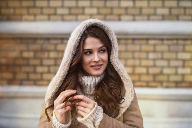 Закройте вверх по портретному фокусу довольной веселой стильной привлекательной красивой молодой счастливой девушки с капюшоном в свитере и куртке, глядя далеко, играя с ее волосами на городской улице. Premium Фотографии