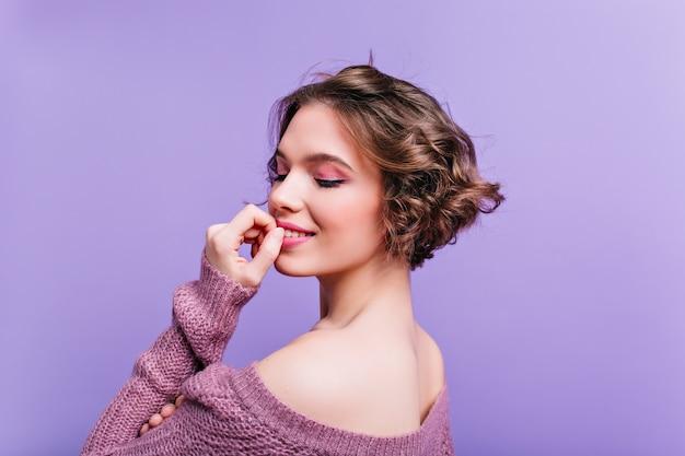 보라색 벽에 포즈 황홀 할 정도로 백인 여성 모델 뒤에서 클로즈업 초상화. 사진 촬영을 즐기는 니트 복장에 기쁘게 짧은 머리 소녀 무료 사진