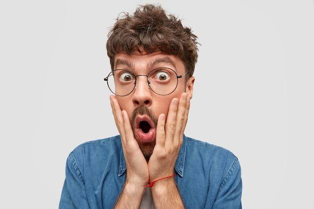 Chiuda sul ritratto del maschio barbuto divertente guarda con sorpresa, tocca le guance e apre la bocca, non può credere in qualcosa, isolato sopra il muro bianco. concetto di persone ed emozioni Foto Gratuite