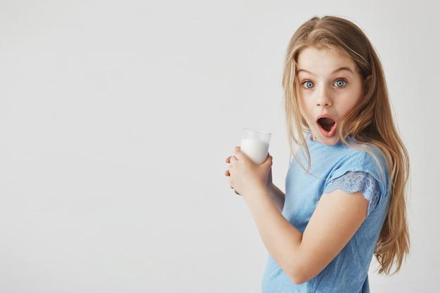 Chiuda sul ritratto di bella bambina divertente con capelli chiari con l'espressione scioccata, tenendo il bicchiere di latte con le mani. Foto Gratuite