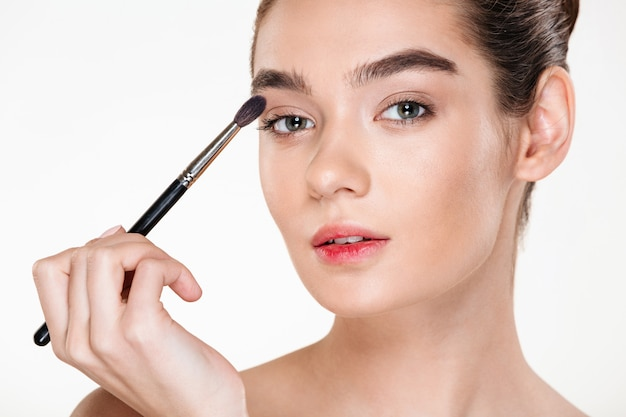 Close up portrait of gentle pretty woman with healthy skin applying make up painting eyes with brush Free Photo