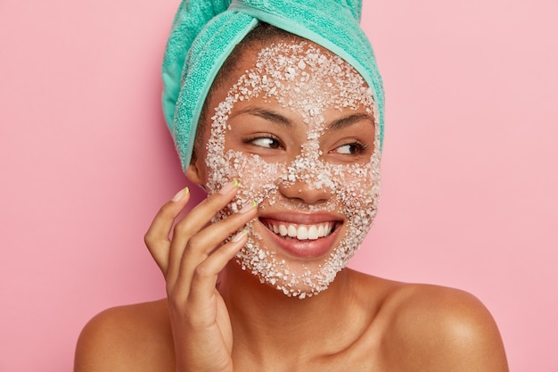 Close up portrait of glad woman massages cheeks, applies sea salt scrub, looks away, has gentle smile, shows white teeth, wears turquoise towel, happy to get spa treatments. Free Photo