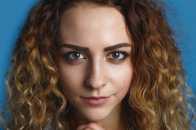 Close up  portrait of gorgeous charming young lady with beautiful sharp green eyes and voluminous hair staring  with mysterious smile. beauty, skin care, style and fashion concept Free Photo