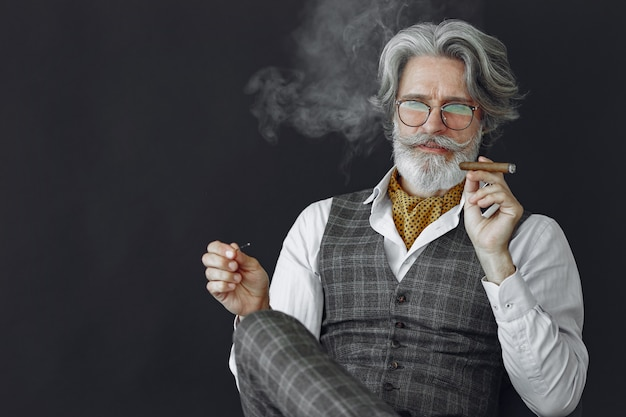 Close up portrait of grinning old-fashioned man.  grandfather with a cigar and whiskey. Free Photo