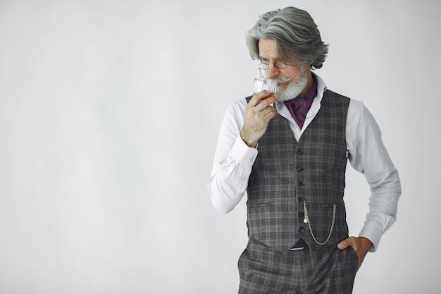 Close up ritratto di ghignare uomo vecchio stile. nonno con un bicchiere di whisky. Foto Gratuite
