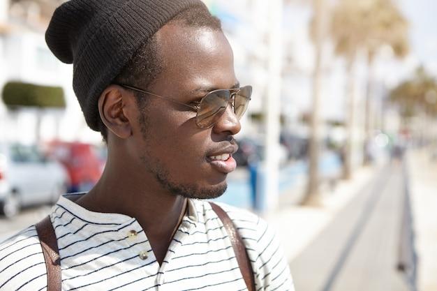 Ritratto del primo piano di bello giovane studente maschio afroamericano in tonalità e copricapo alla moda che hanno bella passeggiata in città straniera nella calda mattina soleggiata mentre trascorrendo le sue vacanze estive all'estero Foto Gratuite